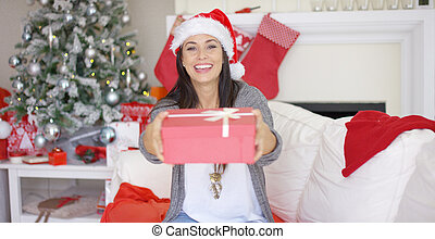Laughing woman offering a large Christmas gift