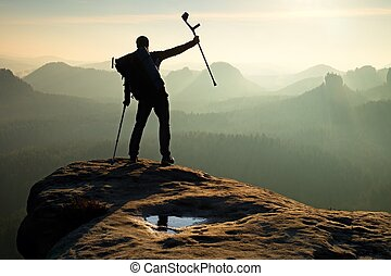 Tourist with medicine crutch above head achieved mountain...
