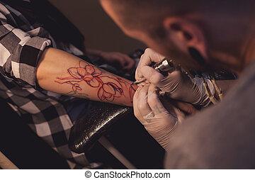 Tattoo artist works in salon - Tattoo artist is inserting...