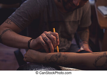 Tattoo artist makes scetch - The tattoo artist is preparing...