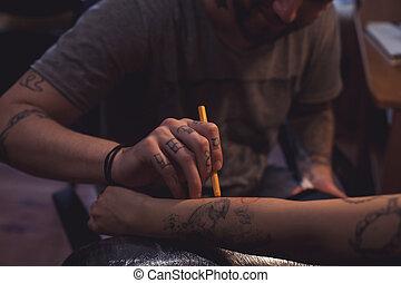 Tattoo artist makes scetch - The tattoo artist is preparing...