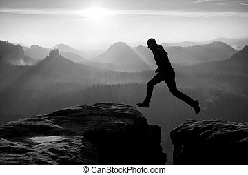 Crazyman in black jump between sharp rocks. - Hiker in black...