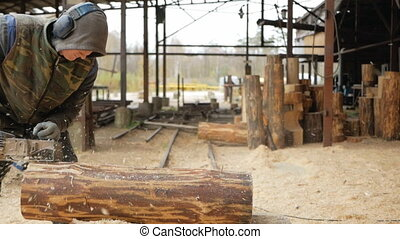 Construction worker planing a piece of wood for a building project. Construction grinds electric hand plane. Against the background of the factory premises, slow motion