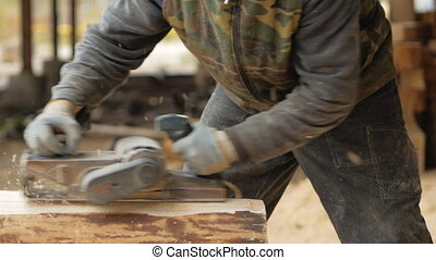 Construction worker planing a piece of wood for a building...