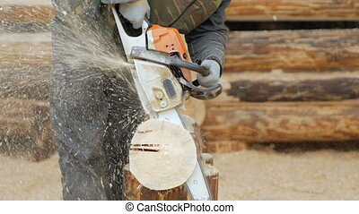 Builder handles wooden timber chainsaw. Against the...
