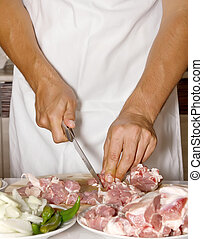 Man cutting the meat on a wooden board - Chef cutting the...