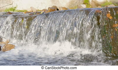 A small waterfall in the park in autumn. Bright sunny day -...
