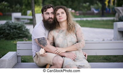 Loving couple in the park. They sit on a bench, embrace and...