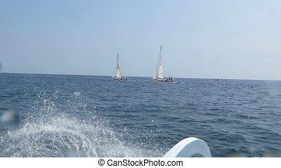 Sailing fishing vessels at sea.