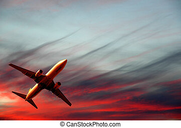 Air travel - plane and sunset - Plane is flying while the...
