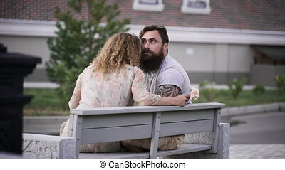 Loving couple in a sunny weather sit on a white bench. They...