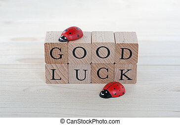 Good luck - The words good luck and ladybugs on wood