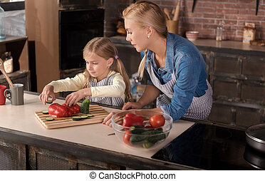 Peaceful caring mother cooking with her daughter in the kitchen