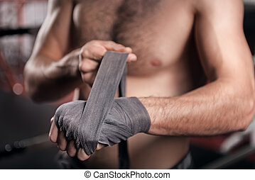 Close up of man wrapping hand in boxing tape - Preparing for...