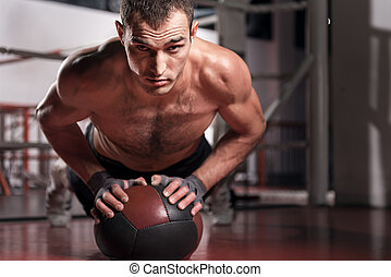 Muscular man doing push-ups with fitness ball