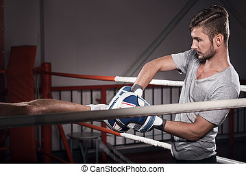 Close up of trainer with boxing pad - During training. Side...