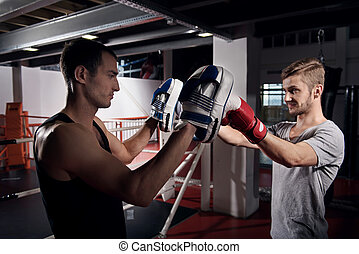 Side view of young boxer training hook on pad - With great...