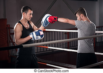 Men practicing boxing on ring - Direct hook. Side view of...