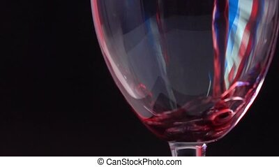 Pouring red wine into glass against black background with...