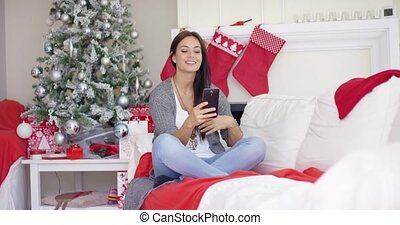 Young woman checking for Christmas messages - Attractive...