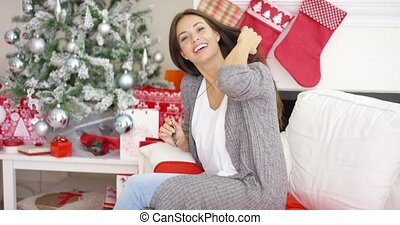 Friendly young woman relaxing at home at Christmas sitting...