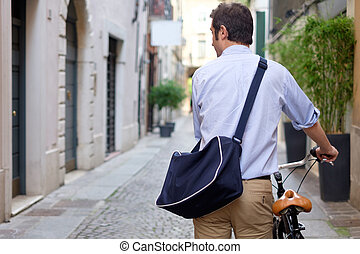 Man is standing next to his bike in the city streets