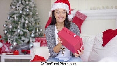 Excited young woman opening a Christmas gift
