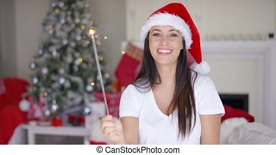 Laughing young woman burning an Xmas sparkler to celebrate...