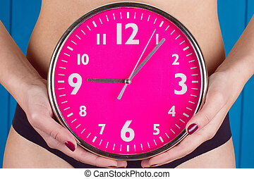 Biological clock ticking . Pink clock in female hands. toning