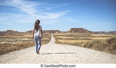 Wild west dirt road - Woman walking on dirt road. Looking...