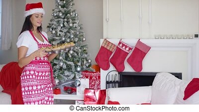 Friendly young woman doing Christmas baking posing in a...