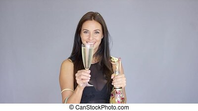 Vivacious woman partying at New Year holding a glass and...
