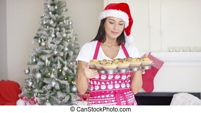 Attractive Christmas cook showing off her cupcakes -...