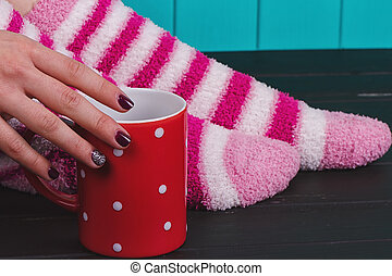 Close-up of female legs in bright colored warm socks -...