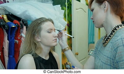 Professional makeup artist applies makeup to a beautiful...