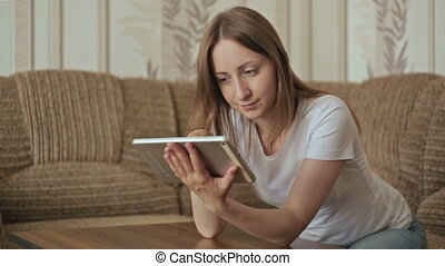 Woman with tablet - Young pretty woman sitting in sofa with...