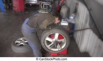 male mechanic balancing car wheel on balancer in repair...