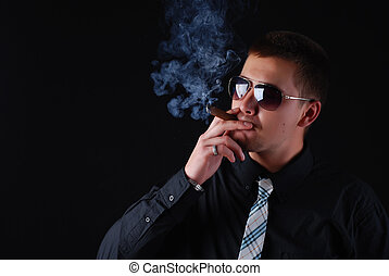 man with cigar - young attractive man in a black suit with...