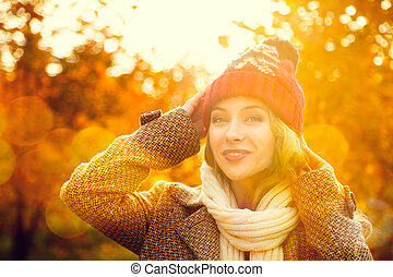 Young Woman in Beanie Hat on Autumn Background in Sunny Day....