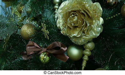 Golden decorations hanging on a Christmas tree. - Golden...