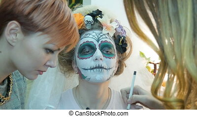 Make-up artist and stylist doing makeup model for Halloween....