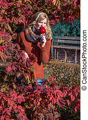 Attractive blonde woman in a park in autumn