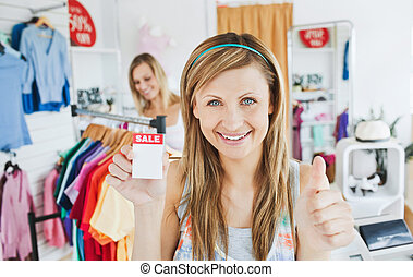 Merry young woman holding a sales paper into the camera with thumb up in a clothes store