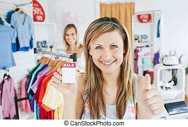 Animated young woman holding a sales paper into the camera with thumb up in a clothes store