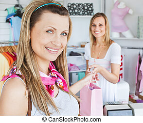 Merry young woman getting shopping bags from the saleswoman