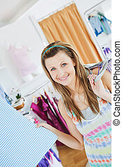 Close-up of a positive woman choosing clothes looking at the camera in a clothes store