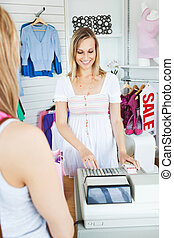 Positive saleswoman standing behind the counter using the...