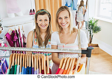 Attractive women smiling at the camera standing in a clothes store doing shopping