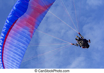 Tandem Paragliding on background of blue summer sky and...