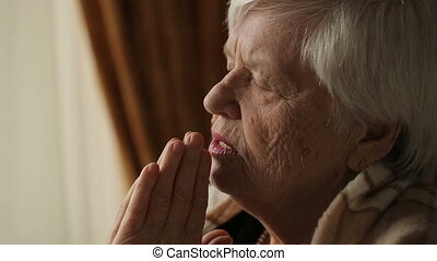 Old woman praying at home - Old woman with deep wrinkles,...